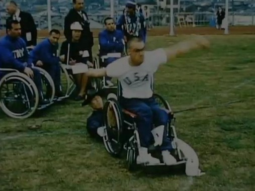 Photo:Discus throwing at Tokyo, 1964. Note the man lying down holding the wheelchair in place.